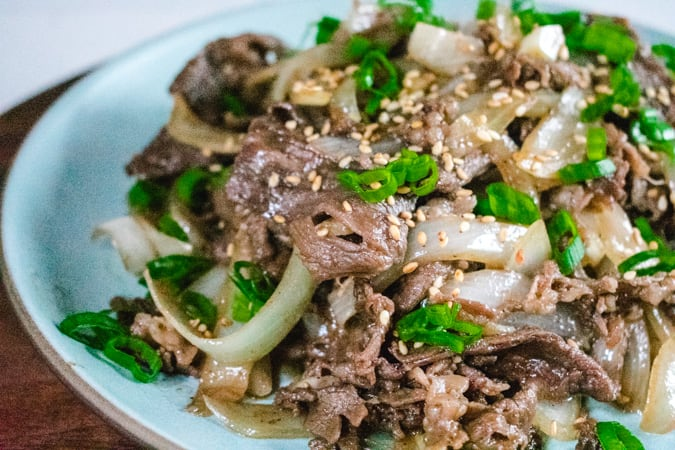 Korean bbq beef and onion with green onion on a blue plate