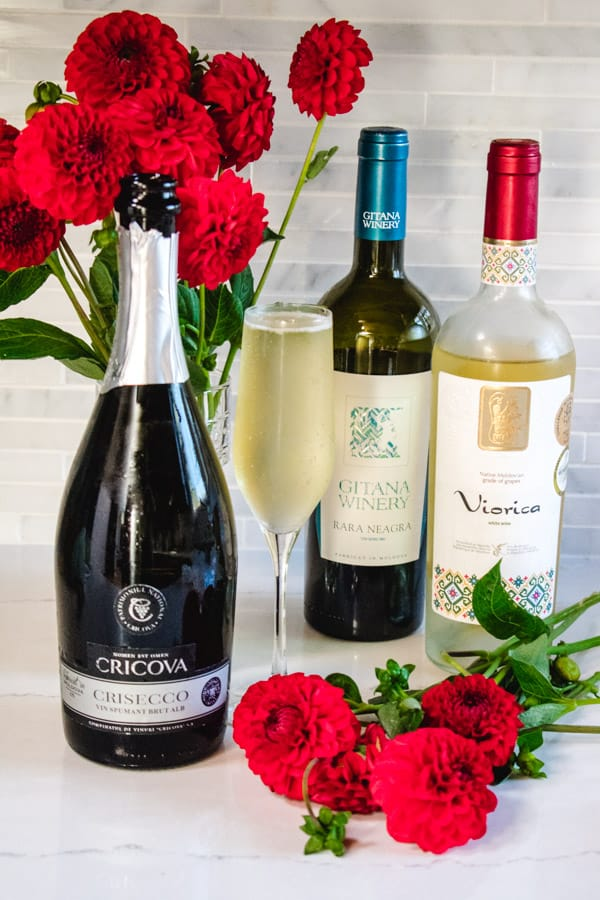 Trio of moldovan wine bottles and flute with red dahlias