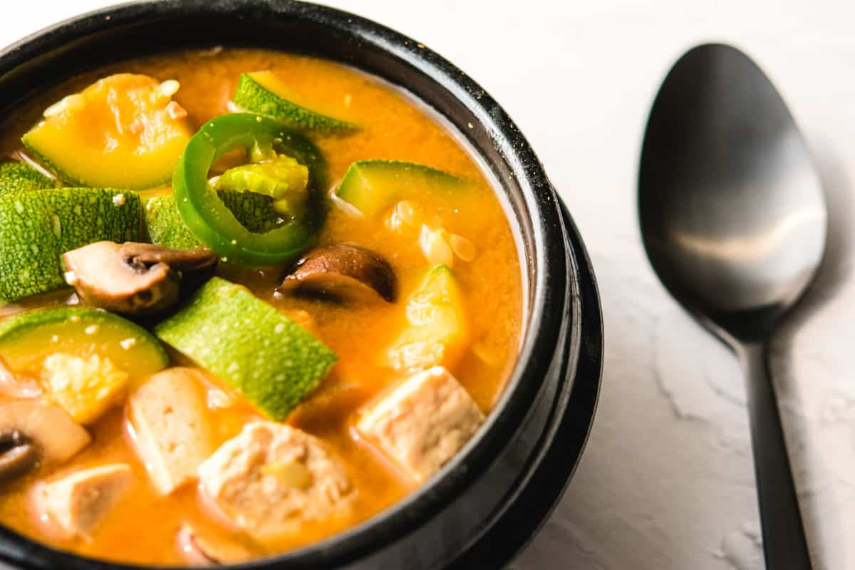 Korean soybean paste stew in a black pot with a black spoon