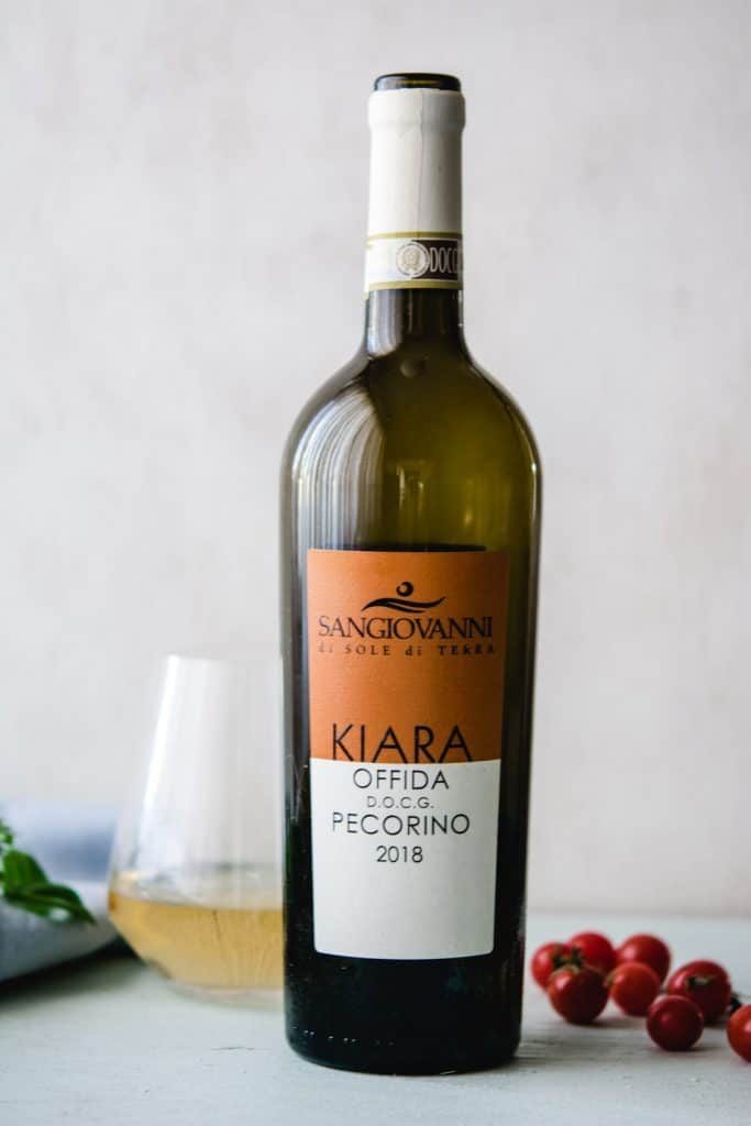 Sangiovanni pecorino vegan wine bottle and glass of wine with cherry tomatoes