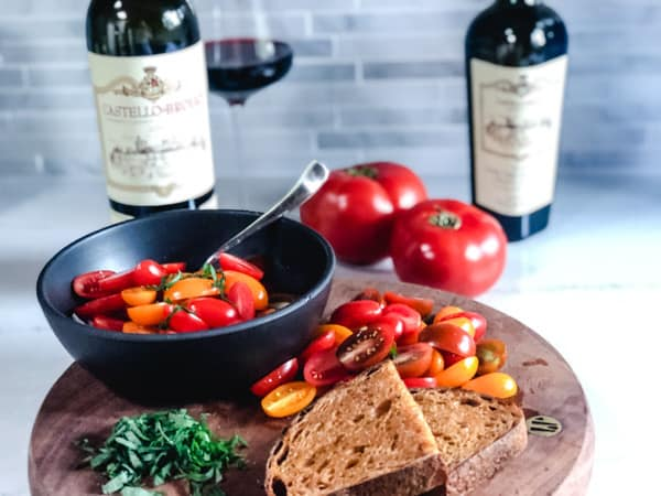 asian tomato salad in a black bowl with bread and tomatoes