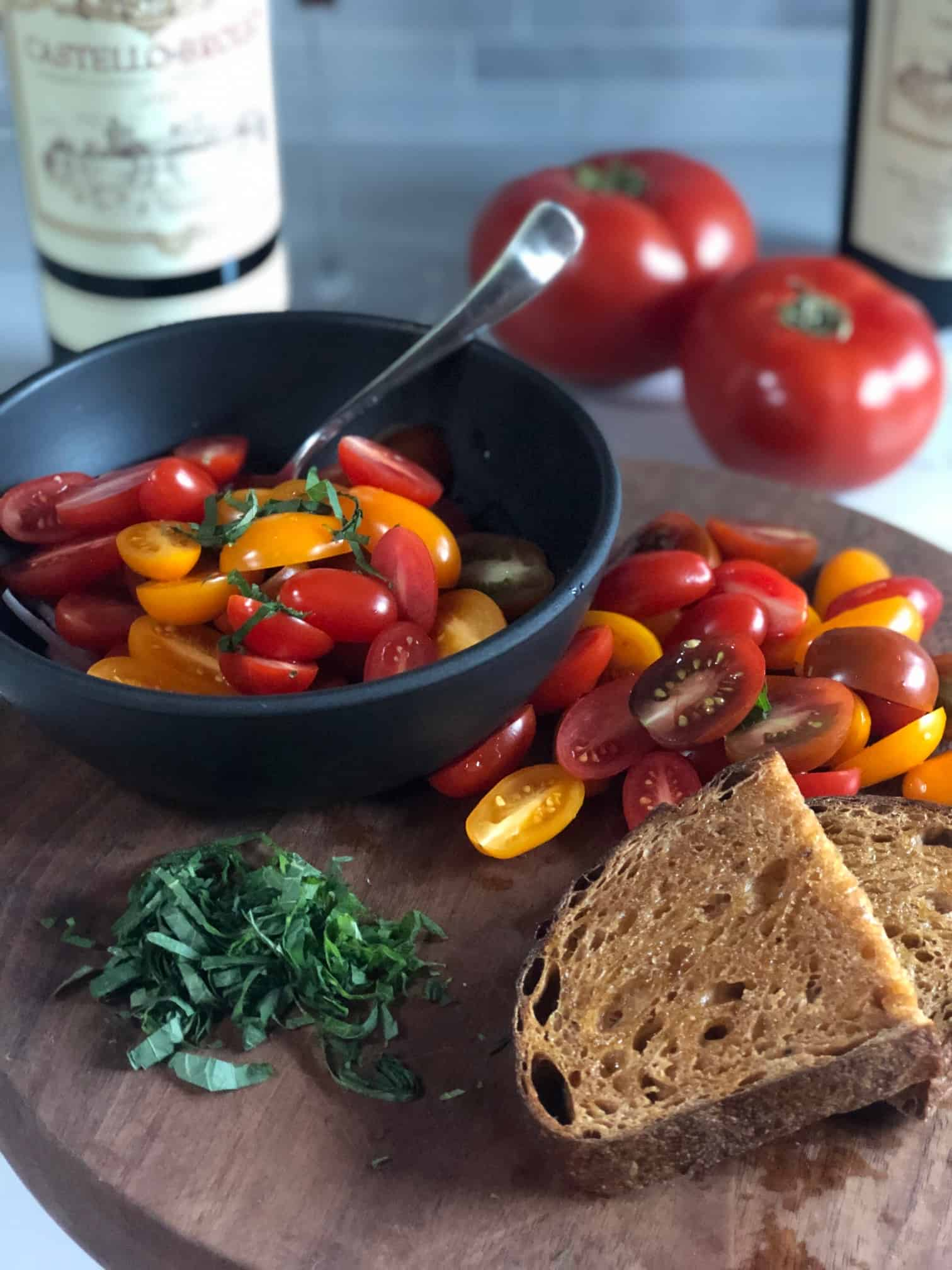 halved cherry tomatoes on a brown cutting board with bread