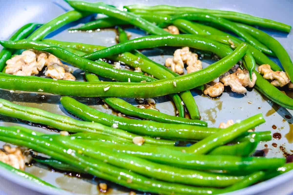raw green beans and walnuts in gray pan