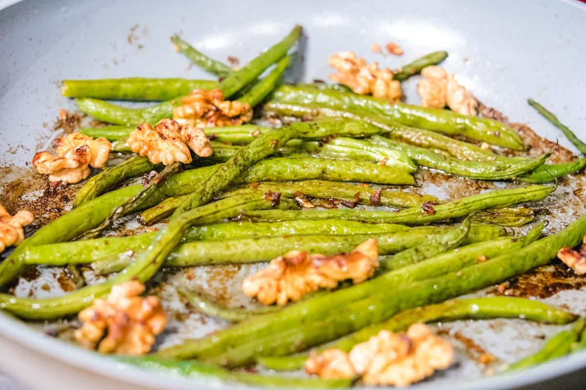 roasted walnuts and green beans in a pan