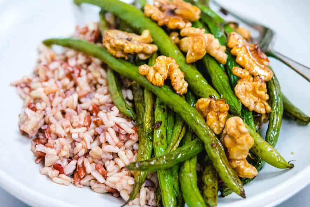 close up of roasted green beans, walnuts, and brown rice in a white bowl