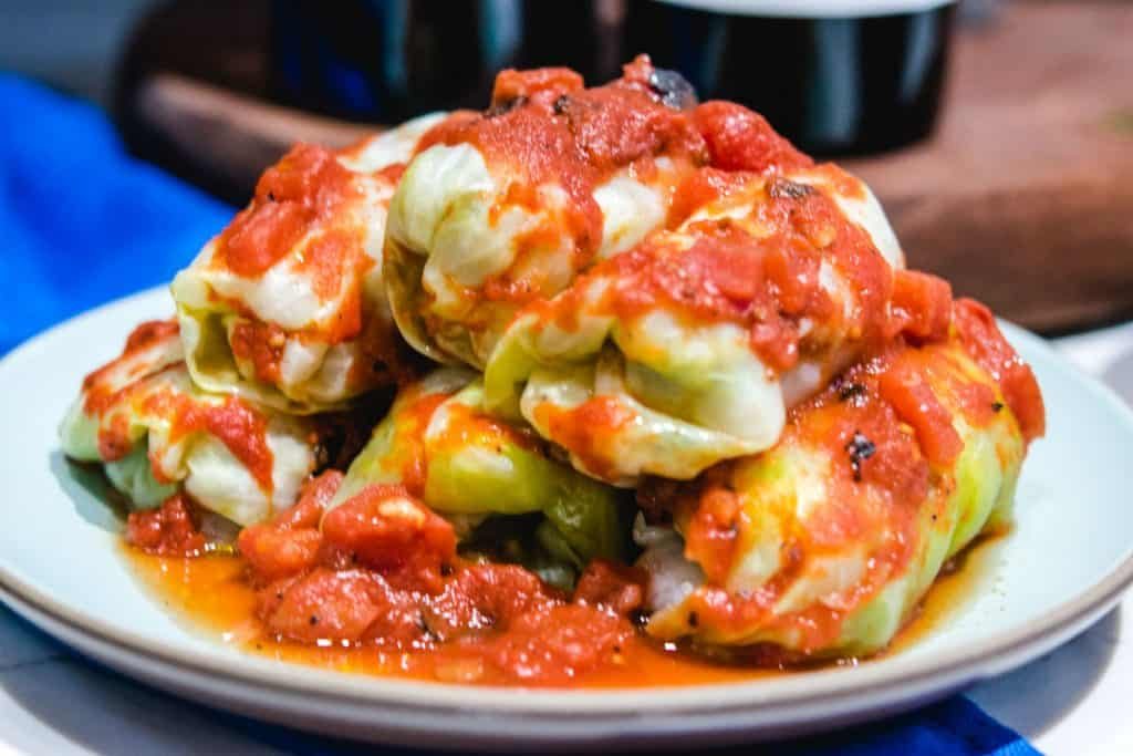round plate of stuffed cabbage rolls with tomato sauce