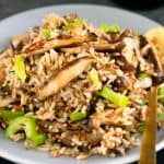 vegan wild rice fried rice on a gray round plate with a gold spoon