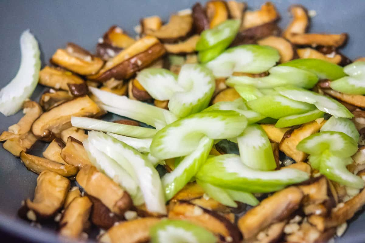 shiitake mushrooms with sliced celery in a wok
