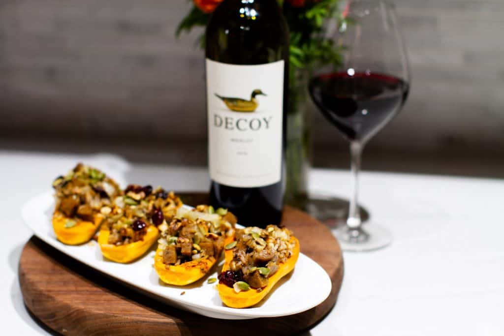 4 stuffed honeynut squash on a plate with Decoy wine in the background