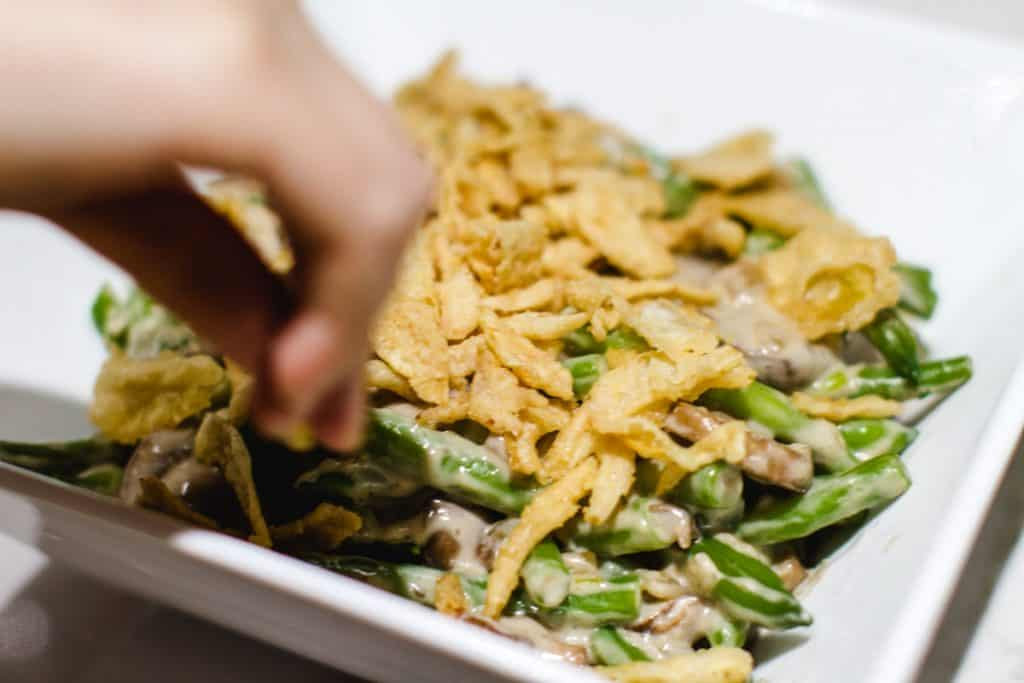 a hand putting fried onions on the green bean casserole