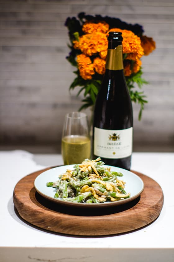 green bean casseroled on a blue plate with a bottle of sparkling wine