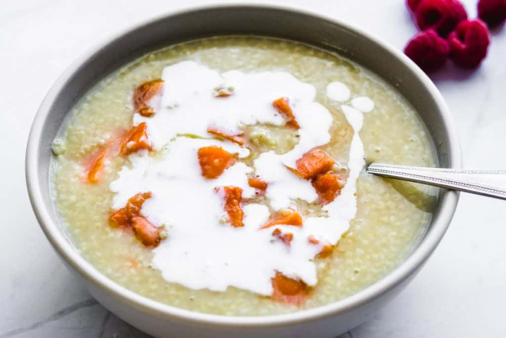 vegan millet porridge with roasted sweet potatoes in a bowl with a spoon and coconut milk