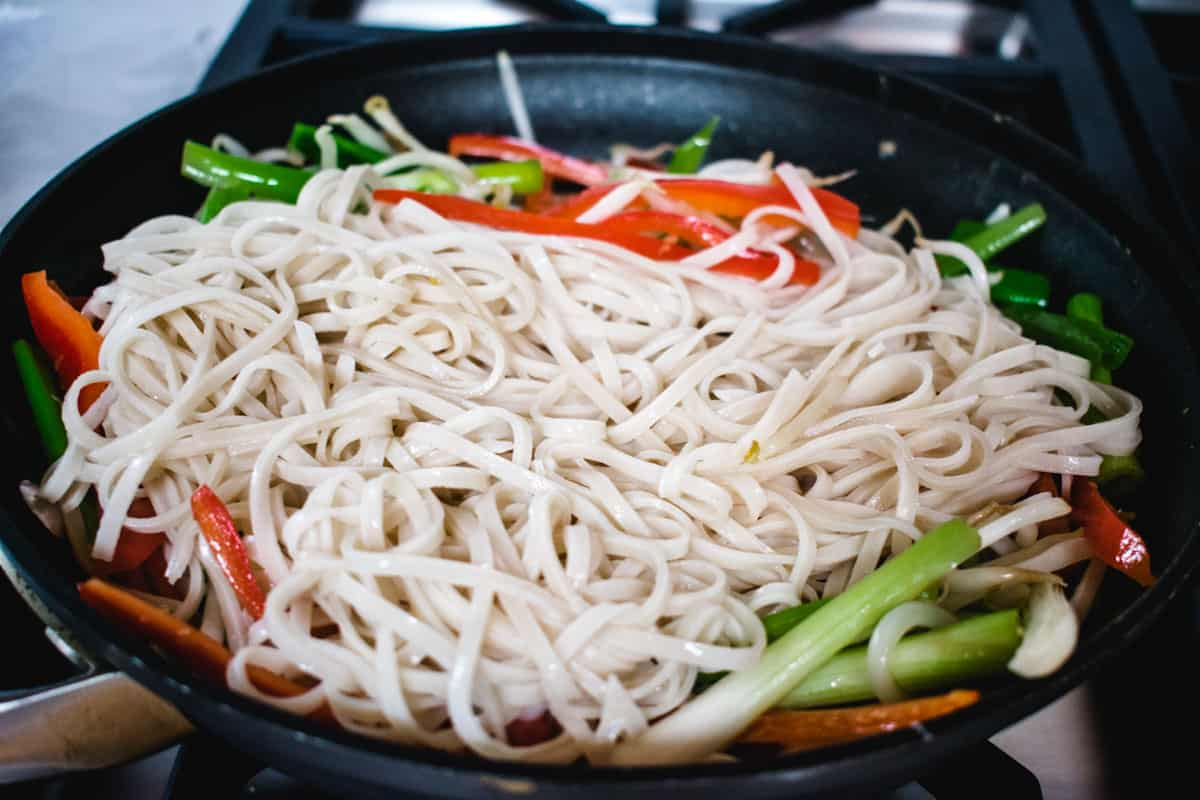 rice noodles in a pan with vegetables