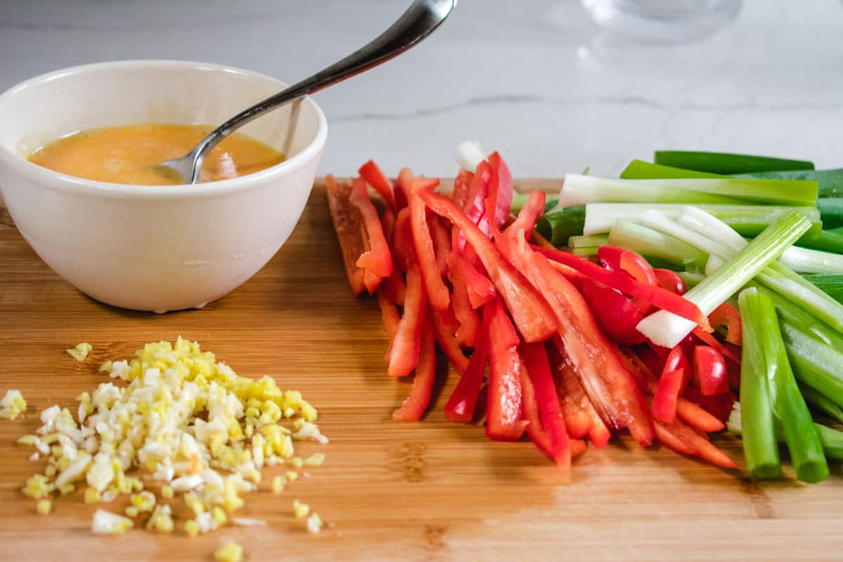chopped vegetables and raw scrambled egg in a bowl