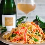 a large pile of shrimp chow fun on a plate with wine in the background