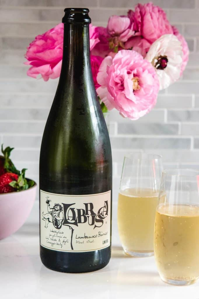 2 glasses of Lini Labrusca Bianco wine with pink flowers in the background
