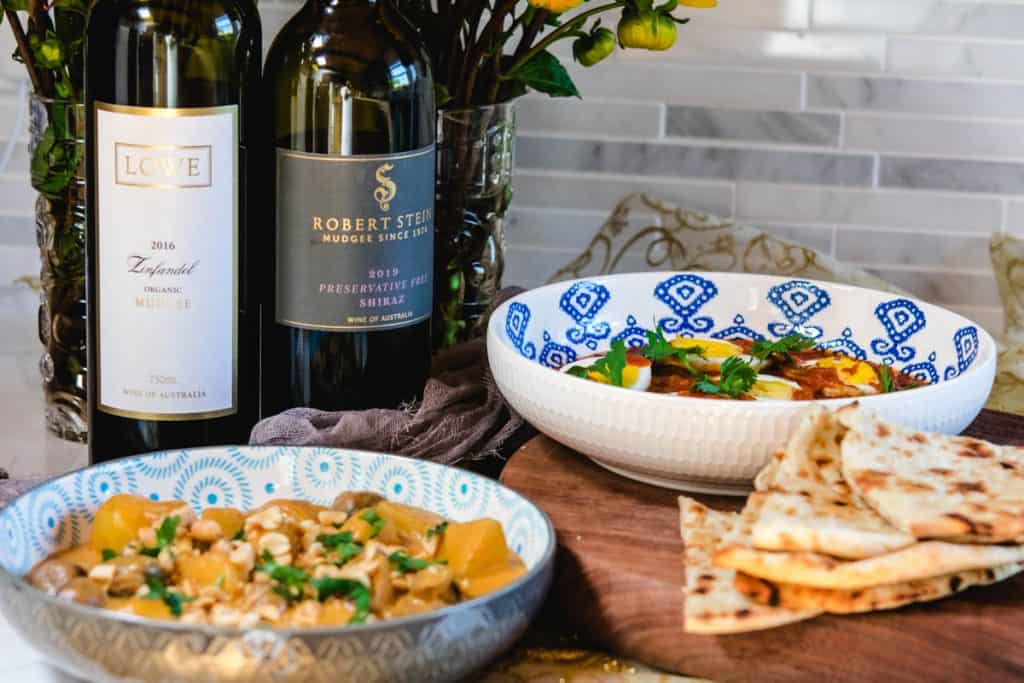2 bowls of curry and naan with 2 mudgee red wine bottles