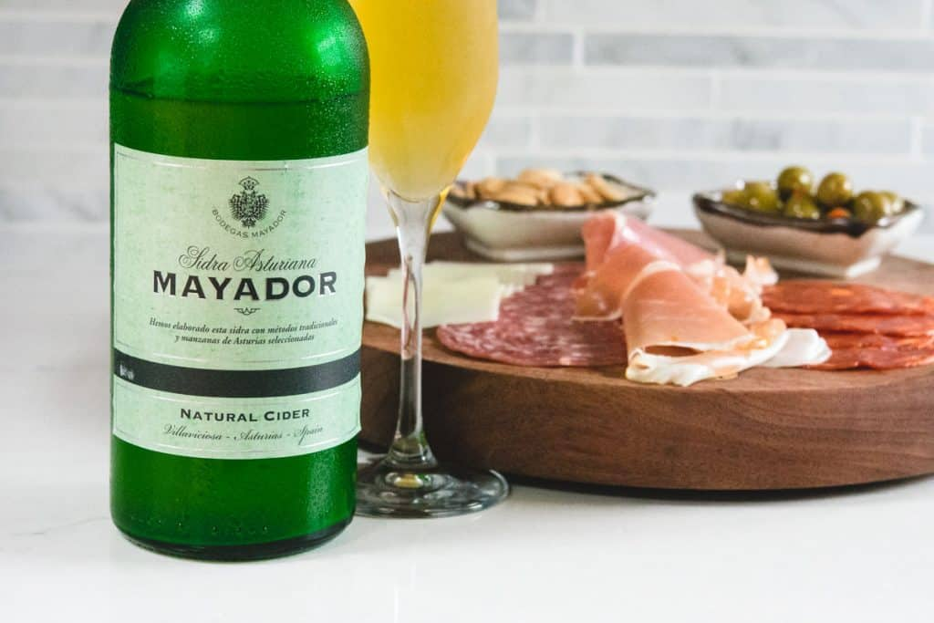 close up shot of mayador cider with charcuterie board